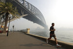 A man jogs under the Sydney Harbour Bridge as a smoke haze hangs over Sydney, Thursday, Nov. 21, 2019. The annual Australian fire season, which peaks during the Southern Hemisphere summer, has started early after an unusually warm and dry winter. (AP Photo/Rick Rycroft)