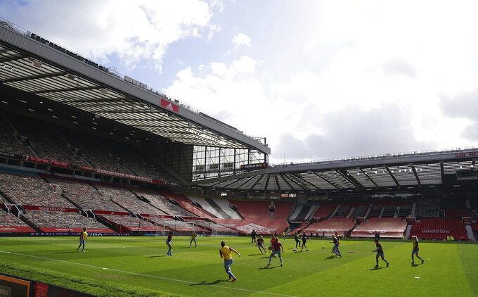 A general view as players warm up before the Women's Super League match between Manchester United and West Ham United at Old Trafford, Manchester, England, Saturday, March 27, 2021. The Manchester United women's team has made its Old Trafford debut in a league game against West Ham. The team normally plays its Women's Super League home matches at Leigh Sports Village but switched to Old Trafford during the international break in the men's game.  (Zac Goodwin/PA via AP)