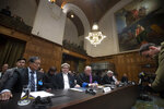 Myanmar's agent, Union Minister Kyaw Tint Swe, left, and members of the delegation take their seats at the International Court in The Hague, Netherlands, Thursday, Jan. 23, 2020. The United Nations' top court is scheduled to issue a decision on a request by Gambia to order Myanmar to halt what has been cast as a genocidal campaign against the southeast Asian country's Rohingya Muslim minority. (AP Photo/Peter Dejong)