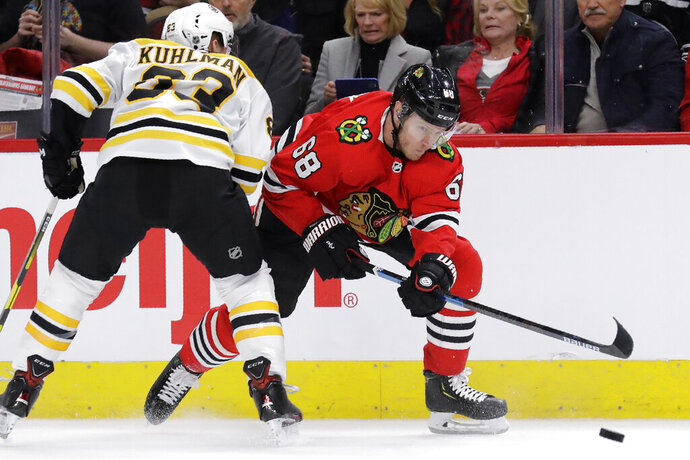 Chicago Blackhawks defenseman Slater Koekkoek, right, controls the puck next to Boston Bruins center Karson Kuhlman during the first period of an NHL hockey game in Chicago, Wednesday, Feb. 5, 2020. (AP Photo/Nam Y. Huh)