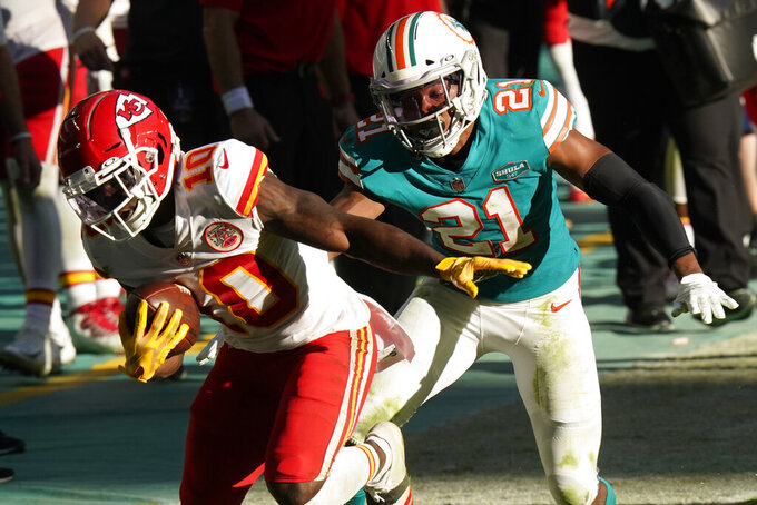 Kansas City Chiefs wide receiver Tyreek Hill (10) runs for a touchdown as Miami Dolphins free safety Eric Rowe (21) attempts to tackle, during the second half of an NFL football game, Sunday, Dec. 13, 2020, in Miami Gardens, Fla. (AP Photo/Lynne Sladky)