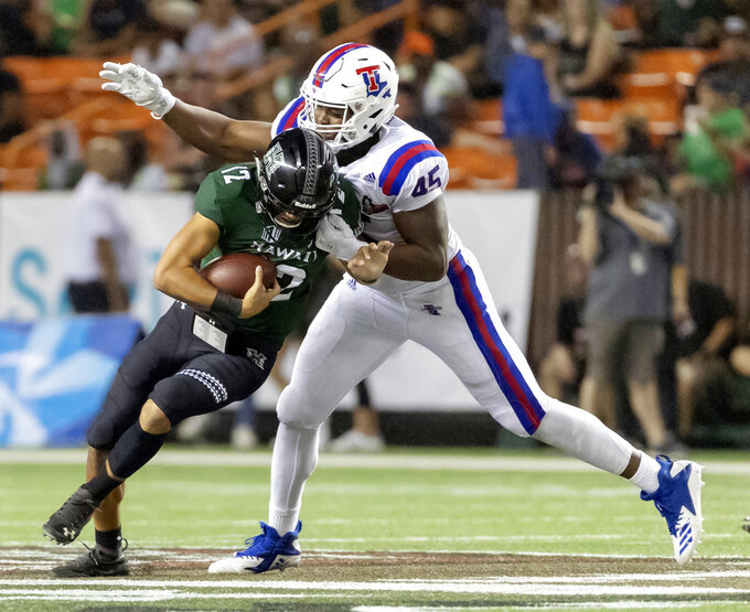 Louisiana Tech defensive end Jaylon Ferguson (45) sacks Hawaii quarterback Chevan Cordeiro (12) in the first half of the Hawaii Bowl NCAA college football game, Saturday, Dec. 22, 2018, in Honolulu. (AP Photo/Eugene Tanner)