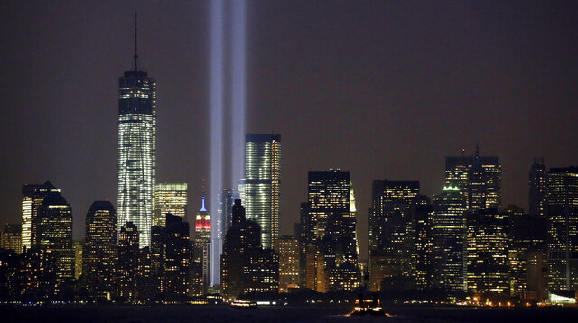 FILE - In this Wednesday, Sept. 11, 2013, file photo, the twin beams of the annual Tribute in Light commemorating the Sept. 11, 2001, terrorist attacks shine amid the city's skyline, in New York. The twin beams of light representing the World Trade Center towers won't be beamed into the sky during the 2020 memorial of the 9/11 terror attacks in New York City, because of concerns about the coronavirus and the health of work crews. (AP Photo/Kathy Willens, File)