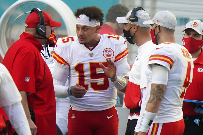 Kansas City Chiefs quarterback Patrick Mahomes (15) talks to head coach Andy Reid on the sidelines, during the second half of an NFL football game against the Miami Dolphins, Sunday, Dec. 13, 2020, in Miami Gardens, Fla. (AP Photo/Wilfredo Lee)