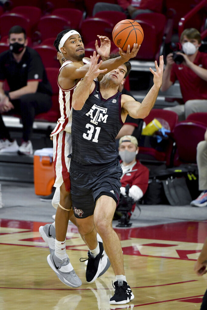Arkansas guard Moses Moody (5) and Texas A&M forward Luke McGhee (31) fight for a rebound during the second half of an NCAA college basketball game in Fayetteville, Ark., Saturday, March 6, 2021. (AP Photo/Michael Woods)