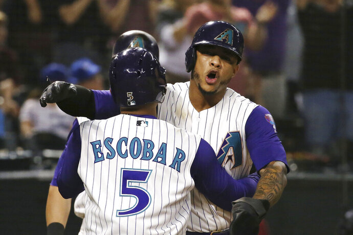 Arizona Diamondbacks' Eduardo Escobar (5) celebrates his three-run home run against the Los Angeles Dodgers with Ketel Marte during the sixth inning of a baseball game Thursday, Aug. 29, 2019, in Phoenix. (AP Photo/Ross D. Franklin)