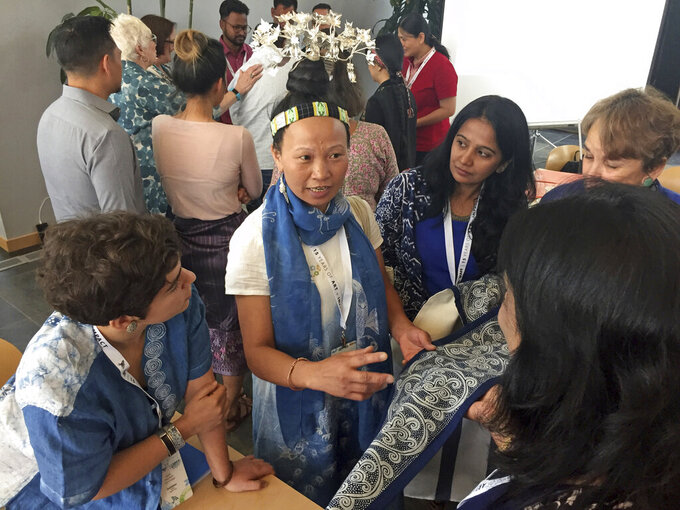 FILE - In this July 11, 2018 file photo Indigo-dye textile artist Yang Xiufen, middle, of the Miao minority group in Guixhou, China, practices her sales pitch at a business workshop that help master folk artists navigate the global marketplace in Santa Fe, N.M. Artists and artisans from more than 50 nations will lose a key source of income and engagement after the International Folk Art Market canceled its annual open-air bazaar in New Mexico due the coronavirus pandemic, event organizers said Tuesday, April 7, 2020. . (AP Photo/Morgan Lee,File)