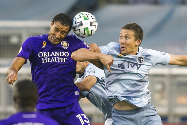 Sporting Kansas City defender Matt Besler (5) goes in for a header against Orlando City forward Tesho Akindele (13) during an MLS soccer game, Wednesday, Sept. 23, 2020 at Children's Mercy Park in Kansas City, Kan. (Nick Tre. Smith/The Kansas City Star via AP)