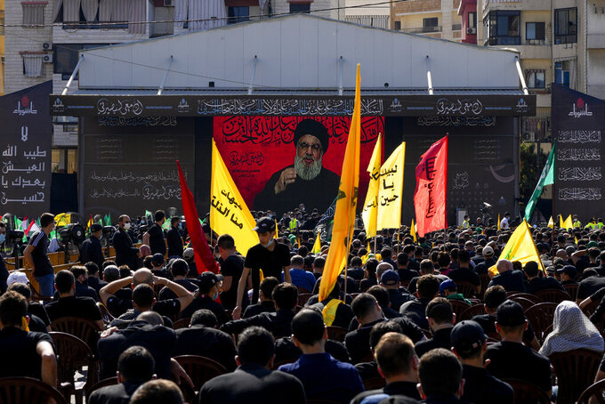 """Hezbollah supporters listen to their leader Sayyed Hassan Nasrallah as he speaks via a video link during Ashoura, the Shiite Muslim commemoration marking the death of Immam Hussein, the grandson of the Prophet Muhammad, at the Battle of Karbala in present-day Iraq in the 7th century, in southern Beirut, Lebanon, Thursday, Aug. 19, 2021. The leader of the militant Hezbollah group Sayyed Hassan Nasrallah said Thursday that the first Iranian fuel tanker will sail toward Lebanon """"within hours"""" warning Israel and the United States not to intercept it. (AP Photo/ Hassan Ammar)"""
