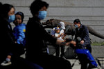 A couple wearing face masks and a child on an electric-powered scooter pass by a man holding an infant as he chats with another man near a sculpture outside a shopping mall in Beijing on Saturday, May 8, 2021. China's population growth is falling closer to zero as fewer couples have children, the government announced Tuesday, May 11, 2021, adding to strains on an aging society with a shrinking workforce. (AP Photo/Andy Wong)