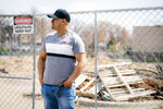 Fidel Martinez stands for a portrait at one of his former worksites in Minneapolis on Sunday, April 18, 2021. Martinez worked for a demolition contractor in the fall of 2020, demolishing several Walgreens stores and other structures. Martinez said the contractor owed him and his co-workers more than $20,000. His boss kept telling him the money was coming, but he would get his paychecks weeks late, and many of them he didn't get at all. (AP Photo/John Minchillo)