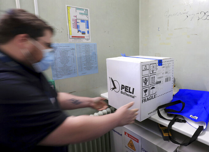 A pharmacy technician from Croydon Health Services prepares to store the first delivery of COVID-19 vaccine at Croydon University Hospital in Croydon, England, Saturday Dec. 5, 2020.  The first batch of Pfizer COVID-19 vaccine is delivered to the area in preparation for public dispersal. (Gareth Fuller/Pool via AP)