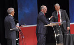 As Eddie Rispone, left, watches, Gov. John Bel Edwards, center, shakes hands with Republican Rep. Ralph Abraham, right, after the trio participated in the first televised gubernatorial debate Thursday Sept. 19, 2019, in Baton Rouge, La. (Bill Feig/The Advocate via AP, Pool)