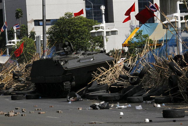 FILE - In this Wednesday May 19, 2010, file photo, an armored vehicle breaks through an anti-government barricade in Bangkok, Thailand. A group of former demonstrators gathered in Thailand's capital on Tuesday to remember those killed when soldiers violently ended a months-long anti-government protest 10 years ago. (AP Photo/Vincent Yu, File)