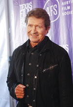 """FILE - Musician Mac Davis appears at the Texas Film Awards in Austin, Texas on March 6, 2014. Davis, a country star and Elvis songwriter,   died on Tuesday, Sept. 29, 2020 after heart surgery. He was 78. Davis started his career writing hits for Presley, including """"A Little Less Conversation"""" and """"In the Ghetto."""" The Lubbock, Texas-native had a varied career over the years as a singer, actor and TV host and was inducted into the Songwriters Hall of Fame in 2006. He was named ACM entertainer of the year in 1974 after the success of songs like """"Baby Don't Get Hooked on Me."""" (Photo by Jack Plunkett/Invision/AP, File)"""