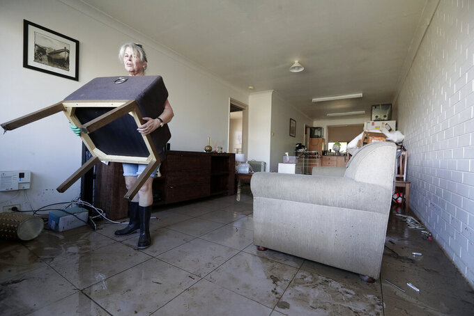 FILE - In this March 25, 2021, file photo, Dale Ward carries water-logged belongings out of her daughter's home after it was flooded in Windsor, northwest of Sydney, Australia. Over recent times, Australia has endured droughts, fires, floods, even a plague of marauding mice. Ward this week was trying to clean out the rental apartment she owns, and where her daughter and their family live, in the town of Windsor. (AP Photo/Rick Rycroft, File)