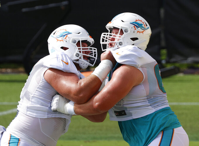 Miami Dolphins center Ted Karras (67), left, and guard Michael Deiter (63) run a drill during an NFL football training camp practice in Davie, Fla., Monday, Aug. 17, 2020. (AP Photo/Joel Auerbach)