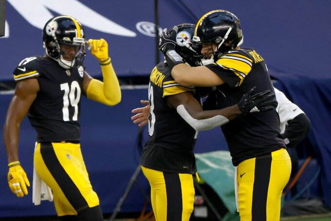 Pittsburgh Steelers' JuJu Smith-Schuster (19), James Washington (13) and Ben Roethlisberger, right, celebrate Washington's touchdown catch in the first half of an NFL football game against the Dallas Cowboys in Arlington, Texas, Sunday, Nov. 8, 2020. (AP Photo/Ron Jenkins)