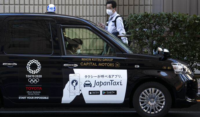 A taxi driver wearing a mask waits for a fare with a Tokyo 2020 logo on the door of his cab Tuesday, Feb. 18, 2020, in Tokyo. Tokyo Olympic organizers said last week there is no