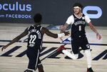 Brooklyn Nets guard Tyler Johnson (8) reacts with guard Caris LeVert (22) after making a three-point basket against the Toronto Raptors during the first half of Game 4 of an NBA basketball first-round playoff series, Sunday, Aug. 23, 2020, in Lake Buena Vista, Fla. (Kim Klement/Pool Photo via AP)