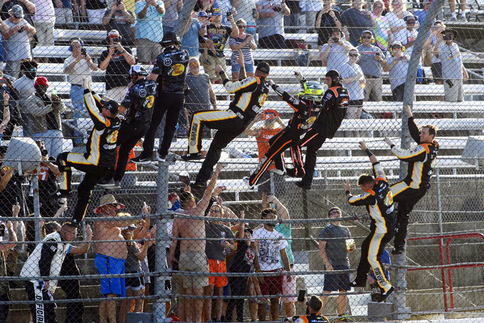 Noah Gragson, in helmet, celebrates with crew members as they climb the fence after winning a NASCAR Xfinity Series auto race Saturday, Sept. 4, 2021, in Darlington, S.C. (AP Photo/John Amis)