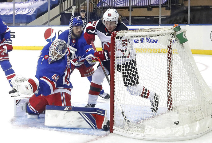 New Jersey Devils' Jack Hughes, right, scores against New York Rangers goalie Alexandar Georgiev during the second period of an NHL hockey game Tuesday, Jan. 19, 2021, in New York. (Bruce Bennett/Pool Photo via AP)