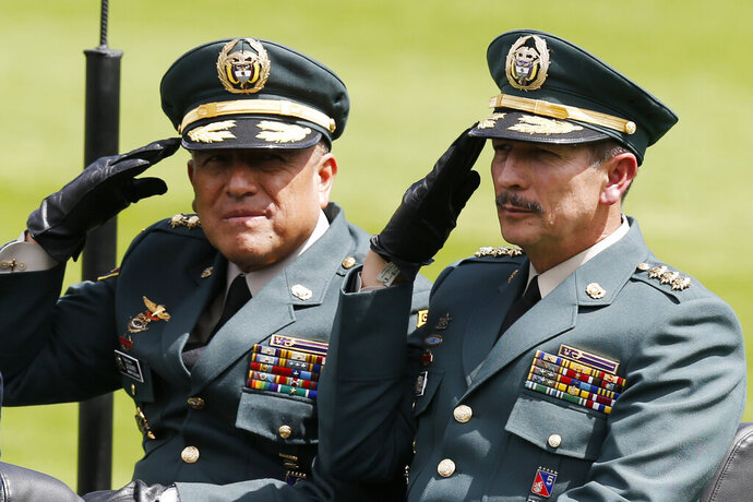 FILE - In this Dec. 17, 2018 file photo, Army Commander Gen. Nicacio Martinez Espinel, right, salutes during a swearing-in ceremony for the new military and police commanders, in Bogota, Colombia. New evidence has emerged linking Martinez Espinel to the alleged cover up of civilian killings more than a decade ago. The documents, provided to The Associated Press by a person familiar with an ongoing investigation into the extrajudicial killings, come as Martinez Espinel faces mounting pressure to resign over orders he gave troops this year, 2019, to step up attacks in what some fear could pave the way for a return of serious human rights violations. (AP Photo/Fernando Vergara, File)