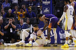 Phoenix Suns' Aron Baynes, left, gets up after falling onto Golden State Warriors' Stephen Curry during the second half of an NBA basketball game Wednesday, Oct. 30, 2019, in San Francisco. Curry left the game. (AP Photo/Ben Margot)