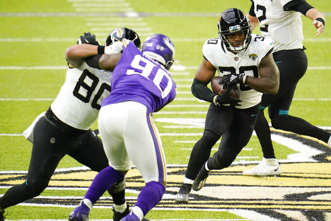 Jacksonville Jaguars running back James Robinson (30) runs from Minnesota Vikings defensive end Jalyn Holmes (9) during the first half of an NFL football game, Sunday, Dec. 6, 2020, in Minneapolis. (AP Photo/Jim Mone)