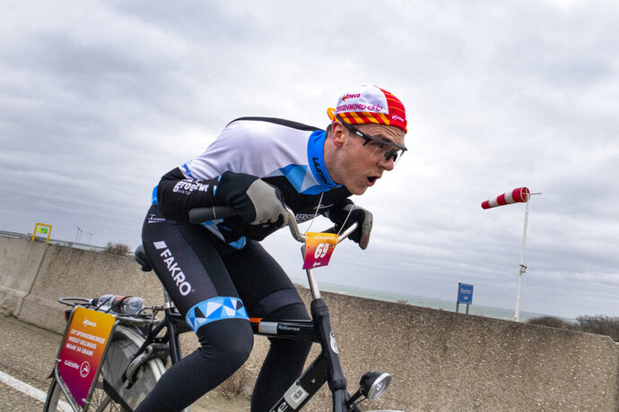 A competitor battles gale force winds during the Dutch Headwind Cycling Championships on the storm barrier Oosterscheldekering near Neeltje Jans, south-western Netherlands, Sunday, Feb. 9, 2020. (AP Photo/Peter Dejong)
