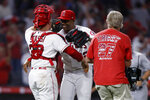 Los Angeles Angels relief pitcher Raisel Iglesias, center, hugs catcher Max Stassi after the Angels defeated the New York Yankees 6-4 in a baseball game in Anaheim, Calif., Tuesday, Aug. 31, 2021. (AP Photo/Alex Gallardo)