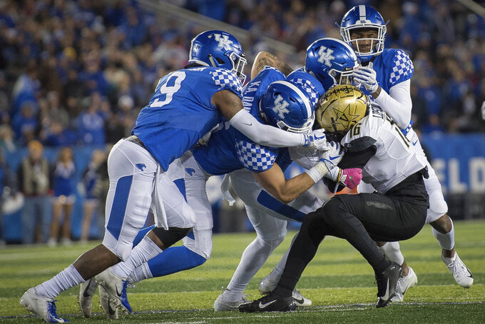 Vanderbilt wide receiver Kalija Lipscomb (16) is tackled by Kentucky defenders during an NCAA college football game in Lexington, Ky., Saturday, Oct. 20, 2018. (AP Photo/Bryan Woolston)