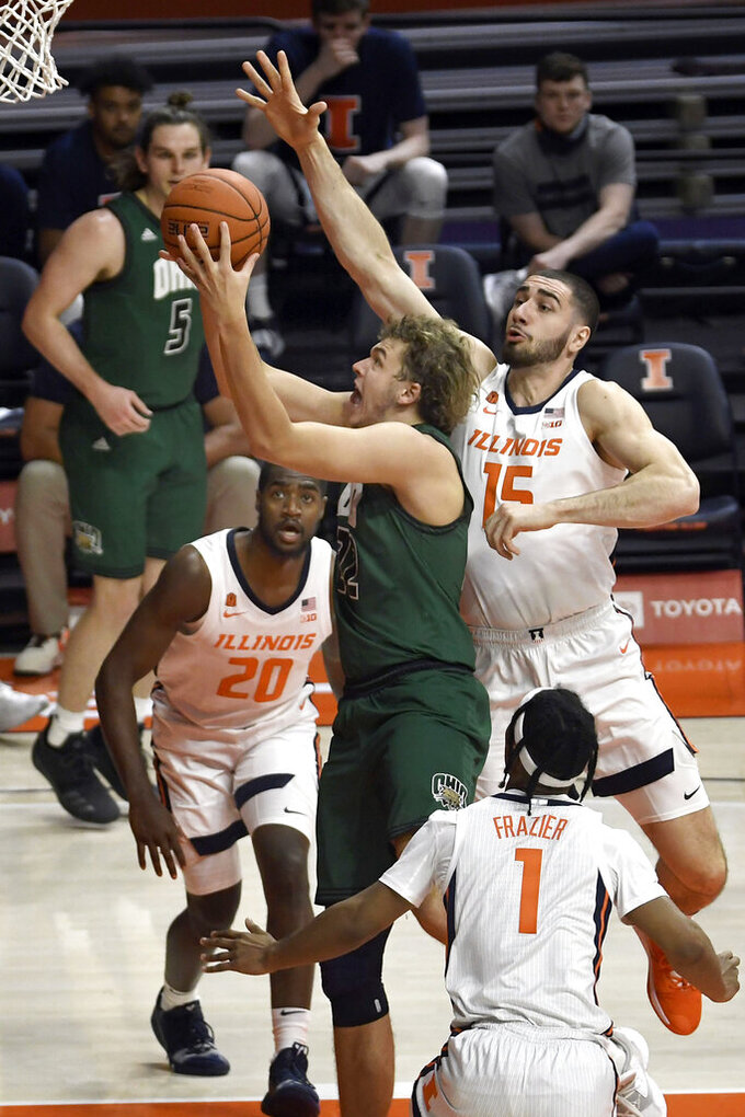 Ohio center Nolan Foster (22) goes to the basket as Illinois guard Da'Monte Williams (20), forward Giorgi Bezhanishvili (15) and guard Trent Frazier (1) defend in the first half of an NCAA college basketball game Friday, Nov. 27, 2020, in Champaign, Ill. (AP Photo/Holly Hart)
