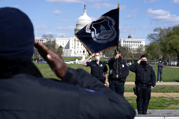 With the U.S. Capitol in the background, a U.S. Capitol Police officer salutes as procession carries the remains of a U.S. Capitol Police officer who was killed after a man rammed a car into two officers at a barricade outside the Capitol in Washington, Friday, April 2, 2021. (AP Photo/Jose Luis Magana)