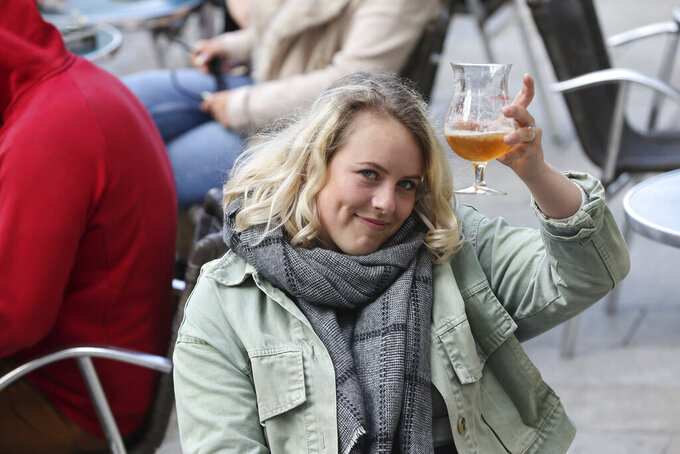 """A woman holds up her beer glass, while seated in a cafe terrace, in Rennes, western France, Wednesday, May, 19, 2021. It's a grand day for the French. Cafe and restaurant terraces are reopening Wednesday after a pandemic shutdown of more than six months deprived people of what feels like the essence of life in France. The French government is lifting restrictions incrementally to stave off a resurgence of COVID-19 and to give citizens back some of their signature """"joie de vivre."""" (AP Photo/David Vincent)"""