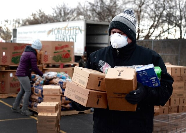 In a photo provided by Project Isaiah, Detroit Health Department worker helps to distribute packaged food as part of the Project Isaiah relief efforts bringing thousands of packaged meals to COVID-positive Detroit residents, Friday, May 1, 2020. (Project Isaiah via AP)
