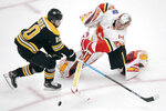 Calgary Flames goaltender David Rittich, right, knocks the puck away from Boston Bruins left wing Anders Bjork (10) during the third period of an NHL hockey game in Boston, Tuesday, Feb. 25, 2020. (AP Photo/Charles Krupa)