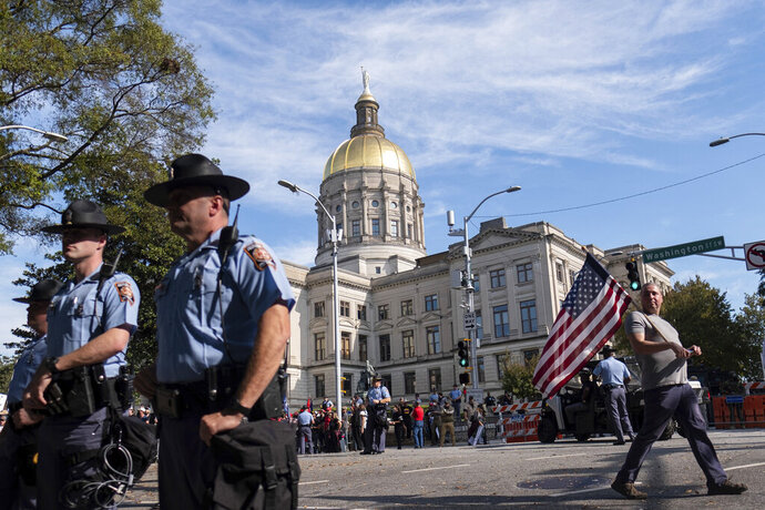 A man carrying an American flag leaves the rally for President Donald Trump outside of the Georgia State Capitol in Atlanta on Saturday, Nov. 21, 2020, and looks down the street at a group of counter protesters. (AP Photo/Ben Gray)