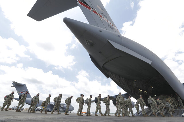 Tennessee National Guard troops board a plane in Smyrna, Tenn., to go to Washington Thursday, June 4, 2020. They are being sent to help with security during protests over the death of George Floyd, a black man who died while being restrained by police in Minneapolis. (AP Photo/Mark Humphrey)