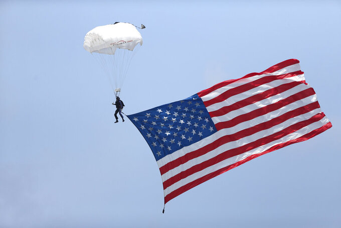 A parachuter displays the American flag during a NASCAR Cup Series auto race in Watkins Glen, N.Y., on Sunday, Aug. 8, 2021. (AP Photo/Joshua Bessex)