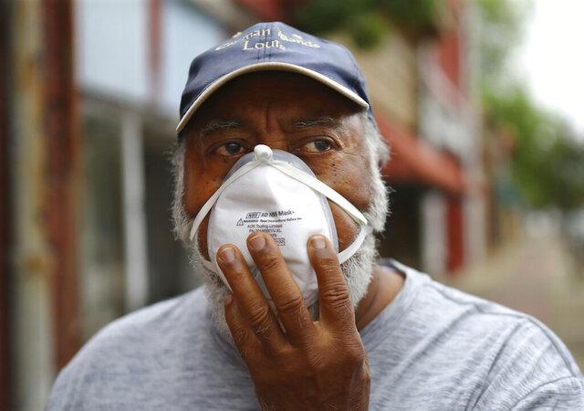 Vietnam veteran Robert Ingram, 74, on West Broad Street adjusts a face mask in downtown Sparta, Ga., Wednesday, May 20, 2020.  Ingram says