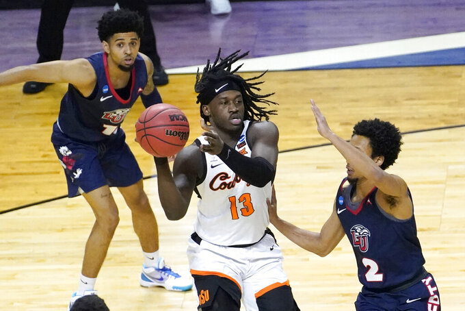 Oklahoma State guard Isaac Likekele (13) passes under pressure from Liberty's Darius McGhee (2) as Chris Parker watches during the first half of a first round NCAA college basketball game Friday, March 19, 2021, at the Indiana Farmers Coliseum in Indianapolis.(AP Photo/Charles Rex Arbogast)