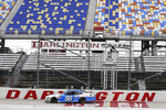 FILE - In this May 21, 2020, file photo, Chase Briscoe (98) passes empty seats during the NASCAR Xfinity Series auto race in Darlington, S.C. In South Carolina, venues ranging from Darlington Speedway to Memorial Stadium at Clemson must submit a plan to the Department of Commerce that lays out how they settled on their attendance number during the coronavirus pandemic. The speedway seats 47,000 but was approved to have 8,000 for the start of NASCAR's playoffs on Sunday (17% of capacity). (AP Photo/Brynn Anderson, File)