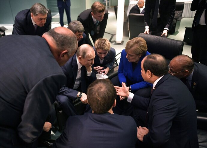 Russian President Vladimir Putin, center left, and German Chancellor Angela Merkel, center right, surrounded by other officials talk to each other during their meeting on the sideline of a conference on Libya at the chancellery in Berlin, Germany, Sunday, Jan. 19, 2020. German Chancellor Angela Merkel hosts the one-day conference of world powers on Sunday seeking to curb foreign military interference, solidify a cease-fire and help relaunch a political process to stop the chaos in the North African nation. (Alexei Nikolsky, Sputnik, Kremlin Pool Photo via AP)