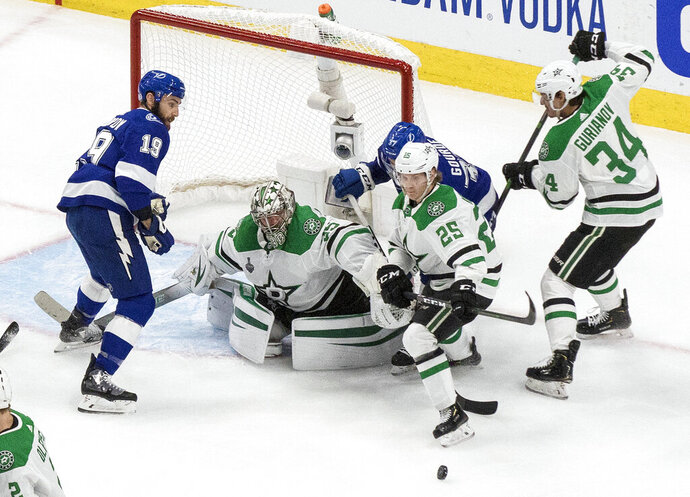 Dallas Stars goalie Anton Khudobin (35) makes a save as Tampa Bay Lightning's Barclay Goodrow (19) and Yanni Gourde (37) battle with Stars' Joel Kiviranta (25) and Denis Gurianov (34) during second-period NHL Stanley Cup finals hockey action in Edmonton, Alberta, Monday, Sept. 21, 2020. (Jason Franson/The Canadian Press via AP)