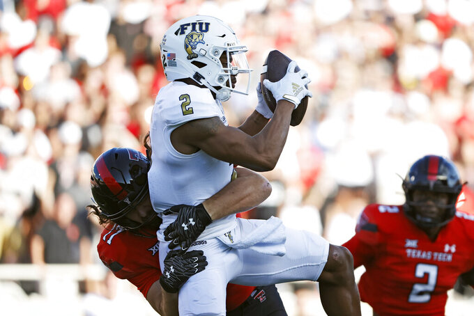Texas Tech's Colin Schooler (17) tackles Florida International's Bryce Singleton (2) during the first half of an NCAA college football game on Saturday, Sept. 18, 2021, in Lubbock, Texas. (AP Photo/Brad Tollefson)