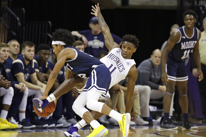 Mount St. Mary's Damian Chong Qui, left, is fouled by Washington's Nahziah Carter during the second half of an NCAA college basketball game Tuesday, Nov. 12, 2019, in Seattle. Washington won 56-46. (AP Photo/Elaine Thompson)
