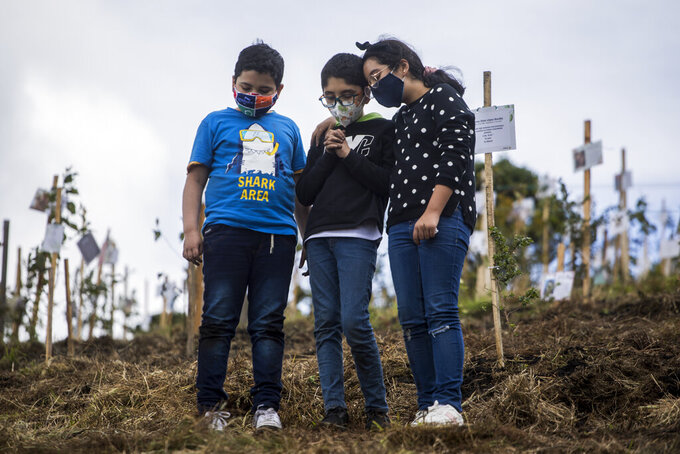 Grandchildren of Alejandro Navas, who died from complications related to COVID-19, stand together after spreading his cremated remains on a hill in the El Pajonal de Cogua Natural Reserve, north of Bogota, Colombia, Thursday, June 24, 2021. As Colombia suffers a critical moment of the pandemic, some families are bringing the cremated remains of their loved ones to the reserve where trees are planted along with the ashes in their honor. (AP Photo/Ivan Valencia)