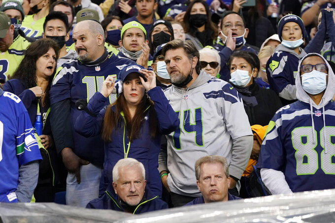 Despite a mask mandate at Lumen Field, most fans go without as they watch during the first half of an NFL football game between the Seattle Seahawks and the Los Angeles Rams, Thursday, Oct. 7, 2021, in Seattle. (AP Photo/Elaine Thompson)