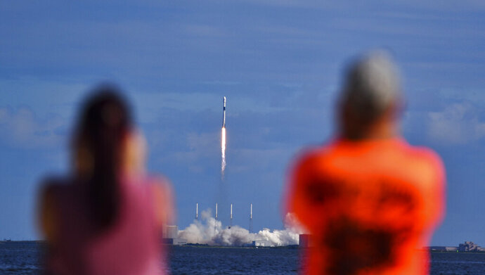 Julie and Doc Todd watch the launch SpaceX from KARS Park in Florida, Monday, Nov. 11, 2019. SpaceX launched 60 mini satellites Monday, the second batch of an orbiting network meant to provide global internet coverage. (Malcolm Denemark/Florida Today via AP)